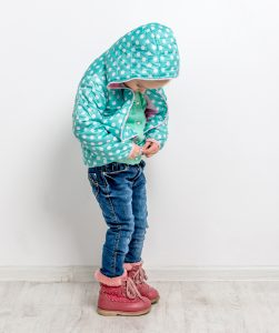 Montessori child doing up jacket